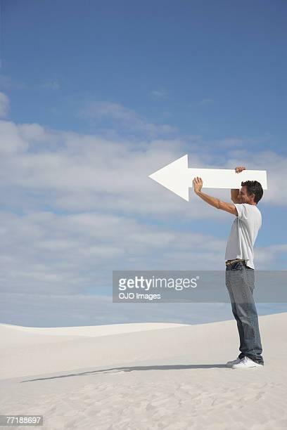 Un homme tenant une Flèche directionnelle