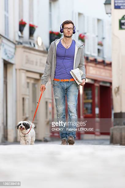 Man holding a dog on leash, Paris, Ile-de-France, France
