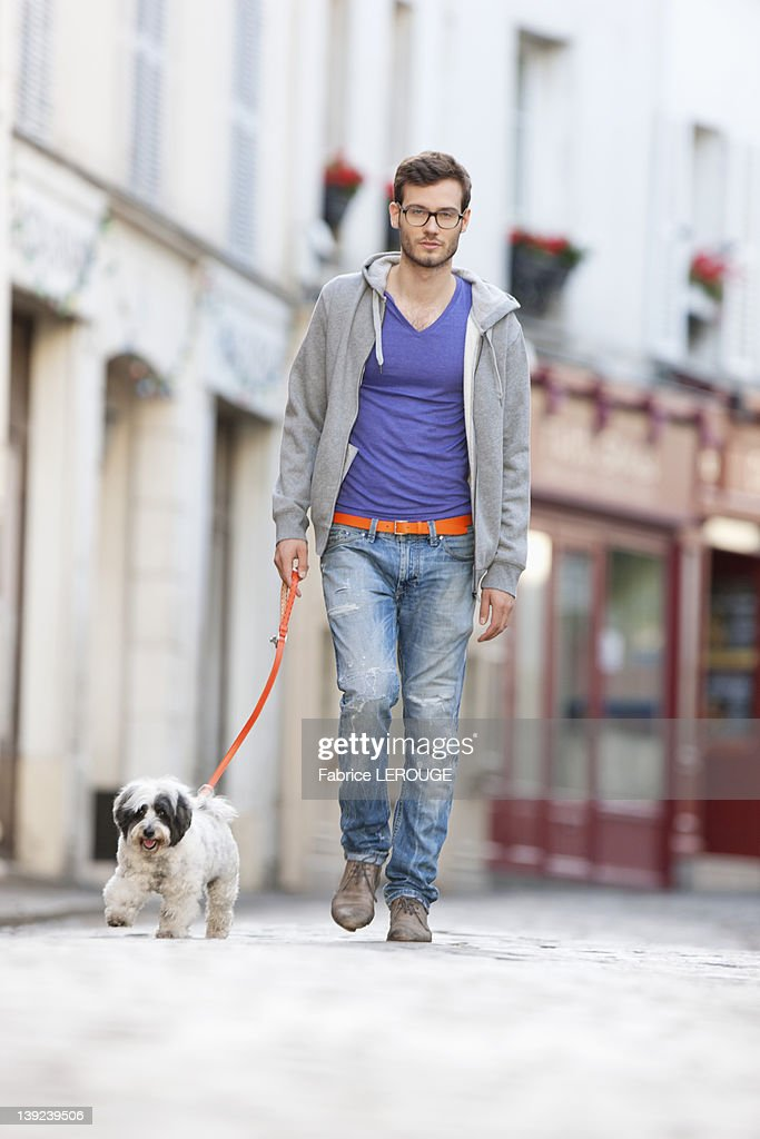Man holding a dog on leash walking on the street, Paris, Ile-de-France, France : Stock Photo