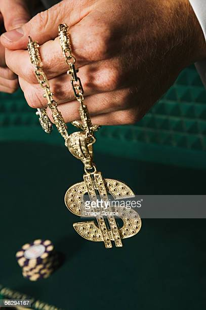 Homme tenant un Symbole du dollar collier