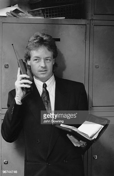 A man holding a Filofax personal organizer and using an early mobile phone at the Daily Express offices in London 20th October 1988