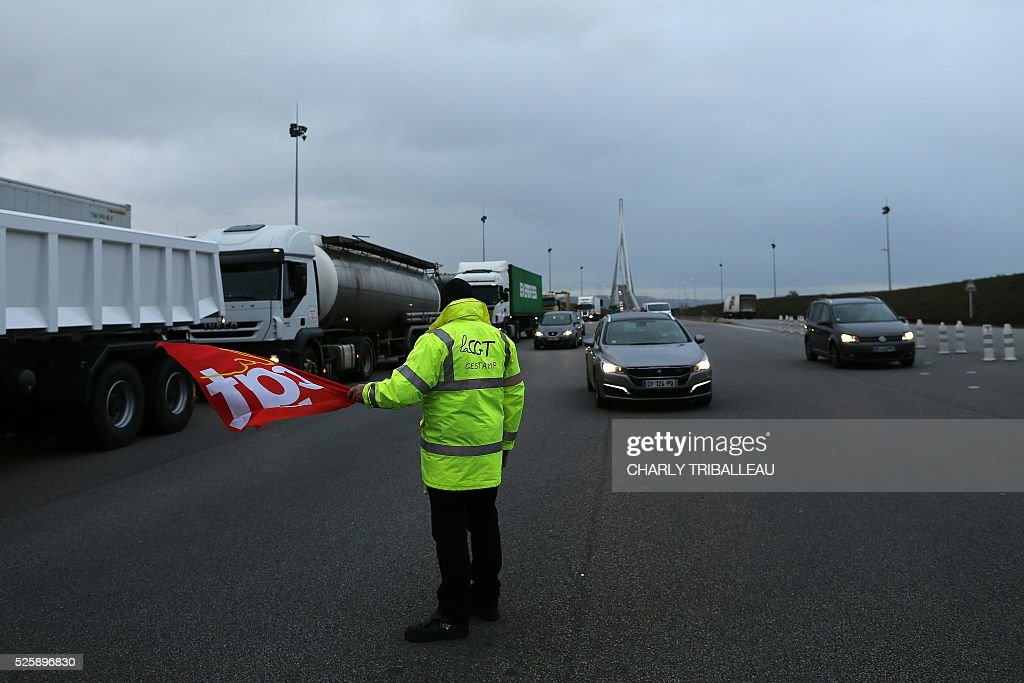 A man holding a flag of the French CGT Trade Union stands guard as he blocks the road at a toll booth on the Normandy Bridge in Le Havre, northwestern France, on April 29, 2016 during a demonstration against the new labour draft-law. / AFP / CHARLY