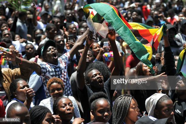 TOPSHOT A man holding a flag of Zimbabwe takes part in a demonstration of University of Zimbabwe's students on November 20 2017 in Harare to demand...