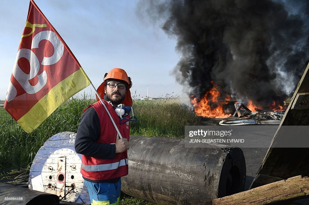 A man holding a French CGT union's flag stands near a fire as workers on strike block the access to an oil depot near the Total refinery of Donges, western France, on May 27, 2016 to protest against the government's planned labour law reforms. The French government's labour market proposals, which are designed to make it easier for companies to hire and fire, have sparked a series of nationwide protests and strikes over the past three months. French unions on May 27 called on workers to 'continue and step up their action', as a wave of strikes against a disputed labour law disrupted transport and fuel supplies. / AFP / JEAN