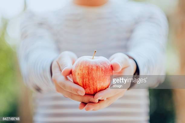 Man holding a fresh red apple in hand in nature