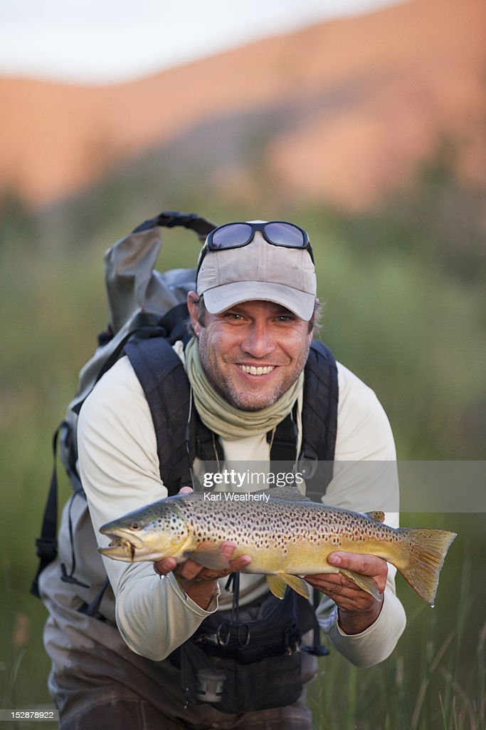 A man holding a freshly caught fish : Stock Photo