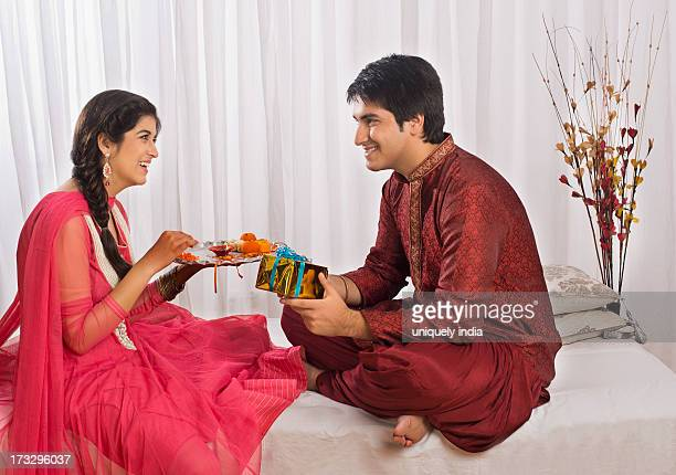 Man holding a gift while his sister holding a puja thali at Raksha Bandhan