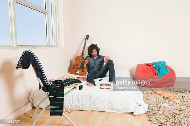 Man holding a guitar in the bedroom
