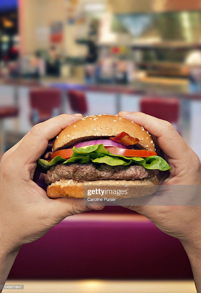 Man holding a hamburger in a diner