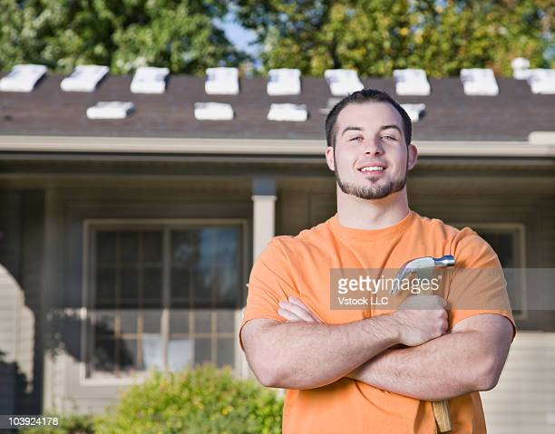 Man holding a hammer in his front yard