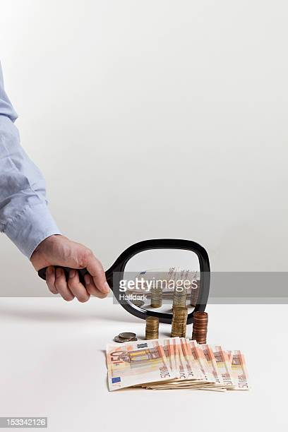 A man holding a hand mirror up to a pile of European Union currency