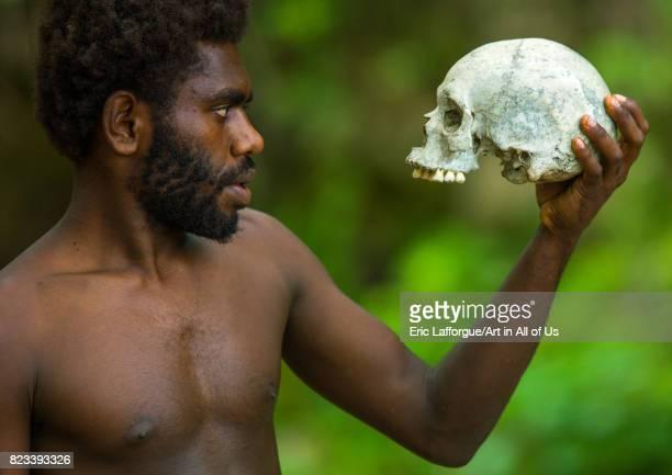 Man holding a human skull in Amelbati cannibal site Malampa Province Malekula Island Vanuatu on August 27 2007 in Malekula Island Vanuatu