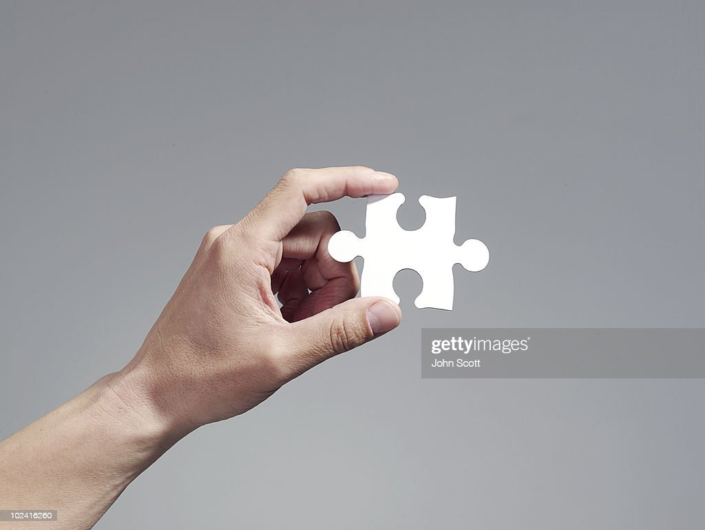 Man holding a jigsaw puzzle piece : Stock Photo