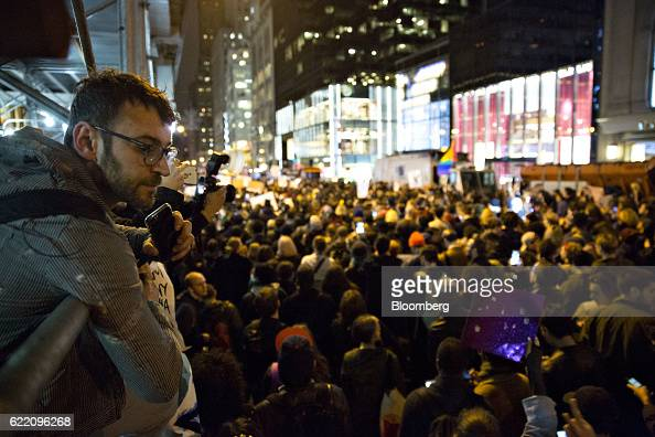A man holding a mobile device looks on as demonstrators gather outside Trump Tower during a rally against US Presidentelect Donald Trump in New York...