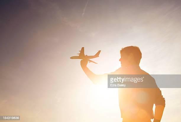 man holding a model plane against sunset.