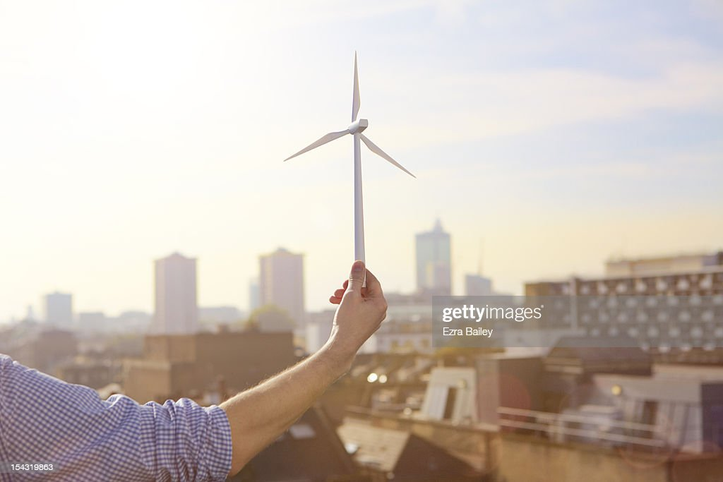 Man holding a model wind turbine.