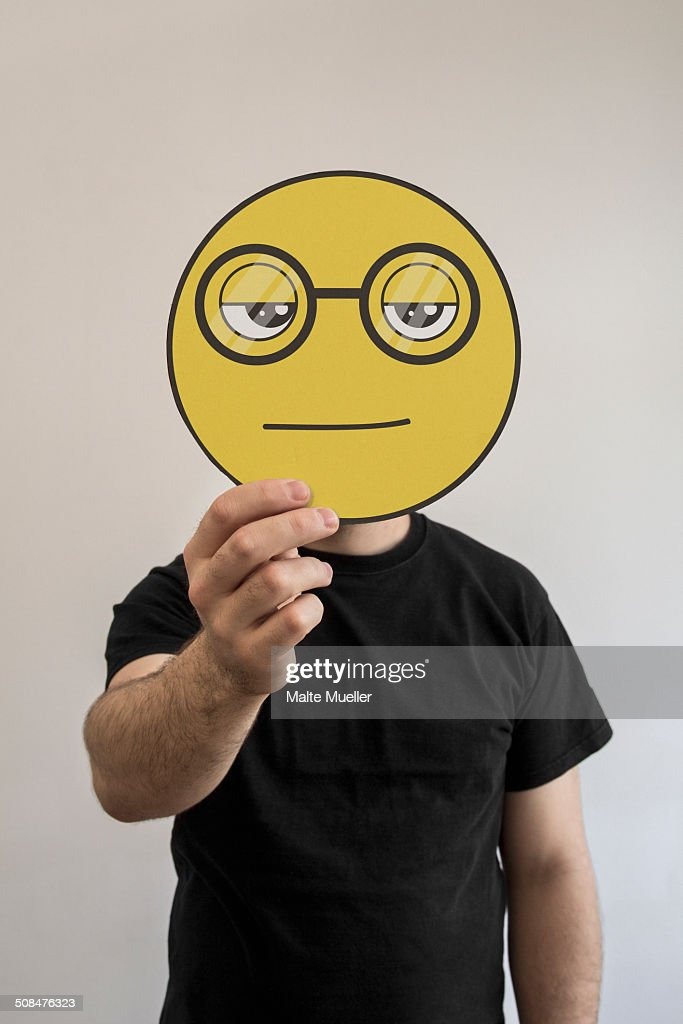 Man holding a nerdy face emoticon face in front of his face
