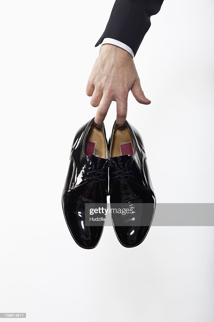 A man holding a pair of patent leather dress shoes, focus on hand