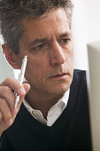Man holding a pen looking at a computer screen