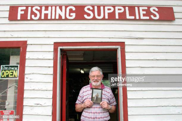 A man holding a picture in the entrance to Charles Bright Fishing Supplies