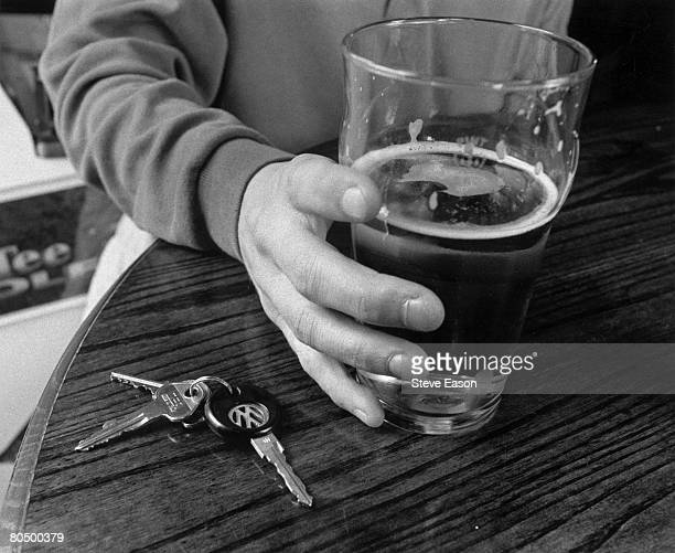 A man holding a pint of lager with his car keys next to it on a table in a British pub 3rd July 1997
