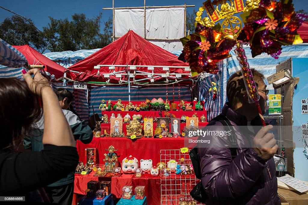 A man holding a pinwheel walks past statues of Buddha displayed for sale at a stall at the Lunar New Year fair in Victoria Park in Hong Kong, China, on Sunday, Feb 7, 2016. The city's financial markets will close on Feb. 8 for the Lunar New Year holidays and resume trading on Feb. 11. Photographer: Billy H.C. Kwok/Bloomberg via Getty Images