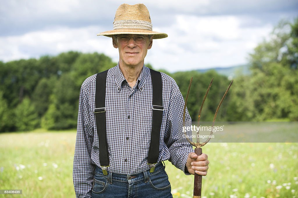 Man holding a pitchfork in the middle of a field. : Stock Photo