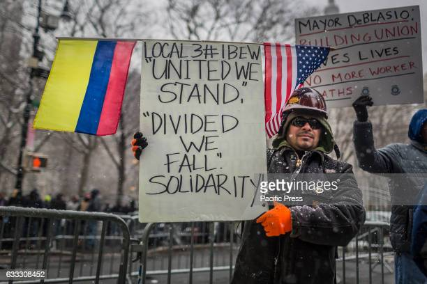 A man holding a placard during the protest Over 30000 members of New York City's Building Trades walked off their jobs to rally outside of City Hall...