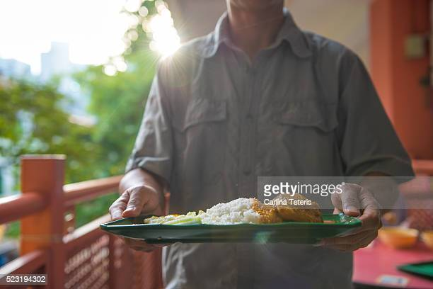 Man holding a plate of nasi lemak with curry chicken in a hawker center