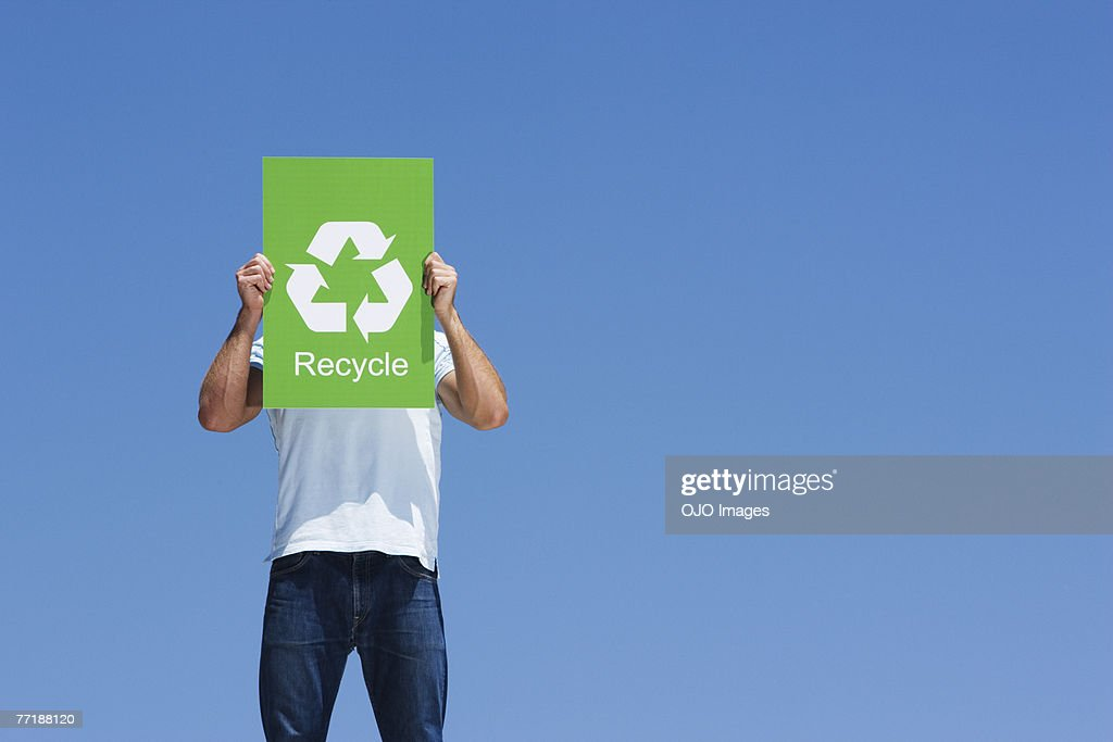 A man holding a recycling sign in front of his face : Stock Photo