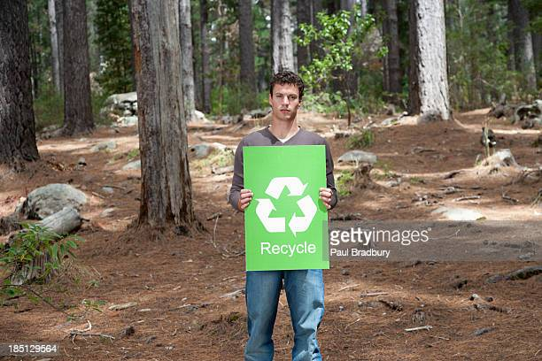A man holding a recycling sign