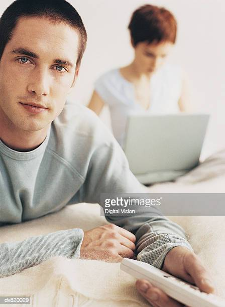 Man Holding a Remote Control with a Woman Using a Laptop