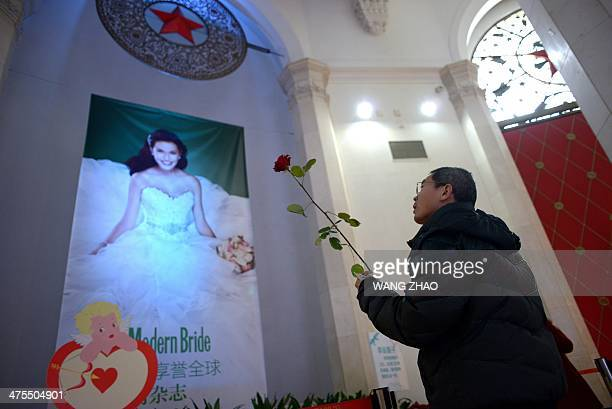 A man holding a rose looks at a poster during a wedding expo in Beijing on February 28 2014 Unlike in the west Chinese wedding photos are normally...