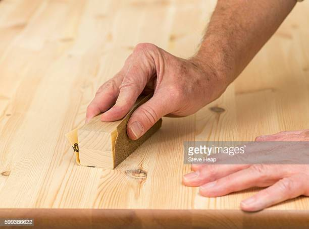 Man holding a sand paper block or sander on pine floor or table sanding surface