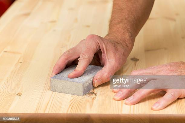 Man holding a sander on pine floor or table sanding surface