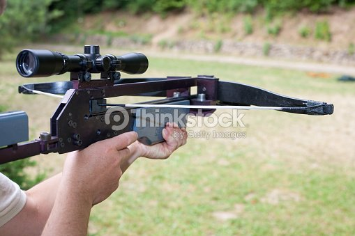 man holding a scoped crossbow ストックフォト thinkstock