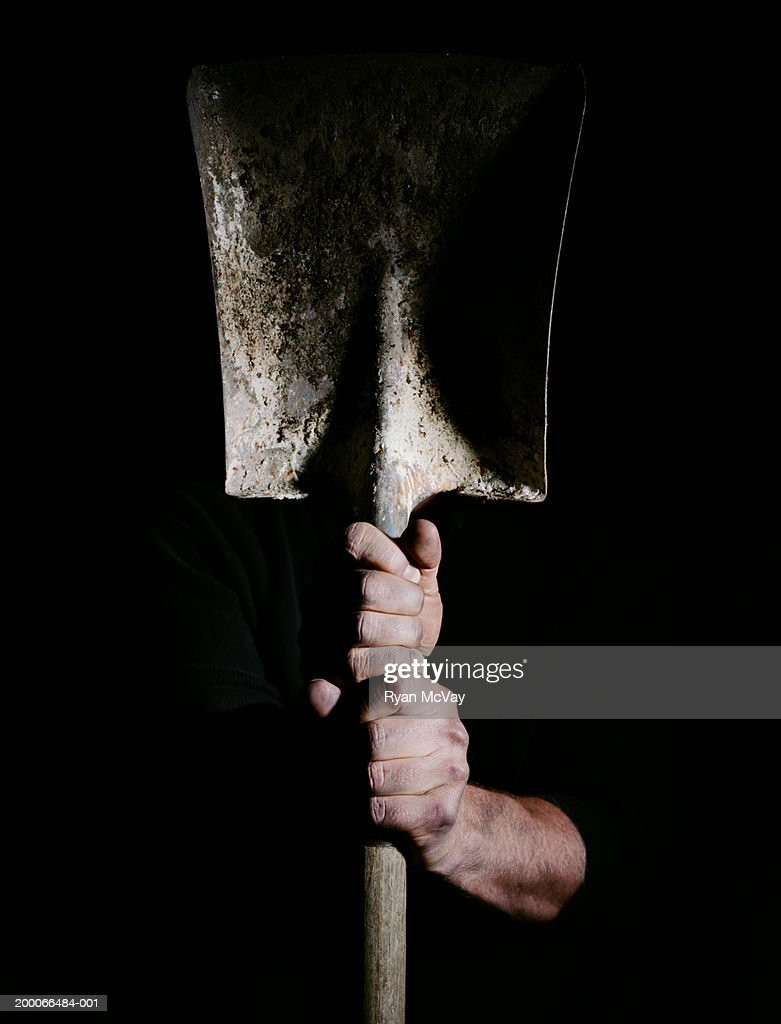 Man holding a shovel, focus on hands : Stock Photo
