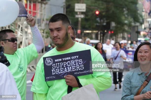 Man holding a sign in support of Deferred Action of Childhood Arrivals during the 2017 Labor Day Parade on Fifth Avenue in New York City New York...