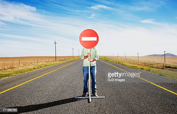 A man holding a sign in the middle of the road