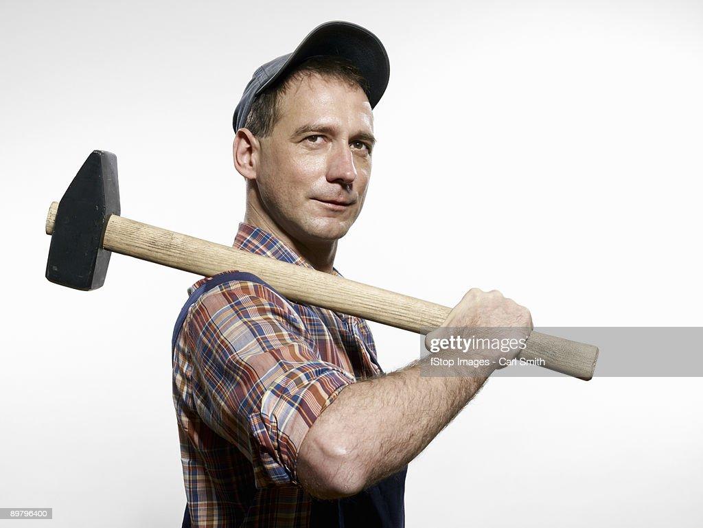 A man holding a sledgehammer over his shoulder