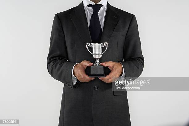 Man holding a small silver trophy.