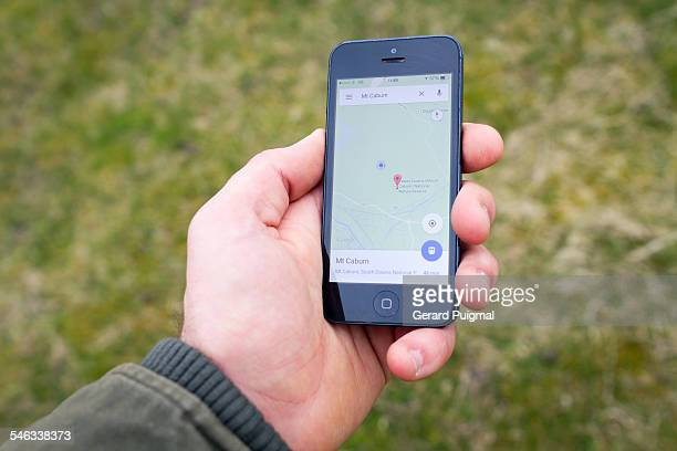 Man holding a smartphone with his hand checking his location on an aplication in the countryside