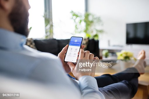 A man holding a smartphone with smart home screen. : Stock Photo