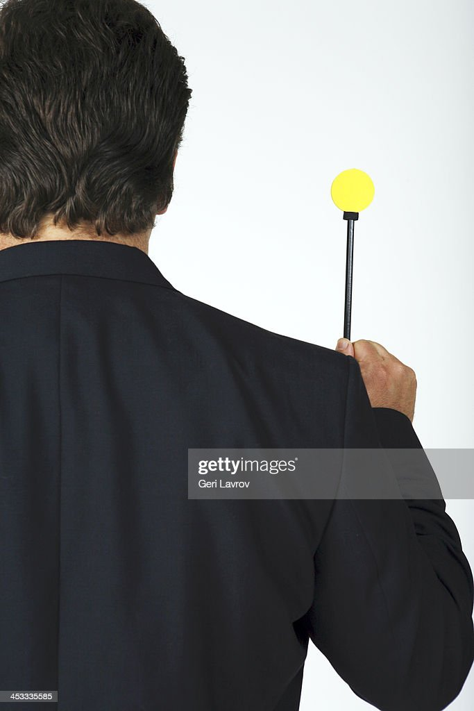 Man holding a stick with a yellow circle : Stock Photo