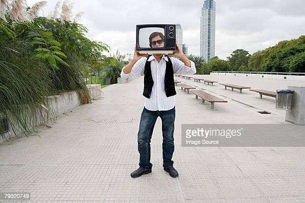 Man holding a television in front of face