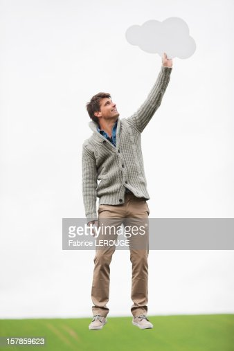 Man holding a thought bubble in a field : Stock Photo