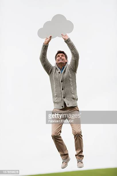 Man holding a thought bubble in a field