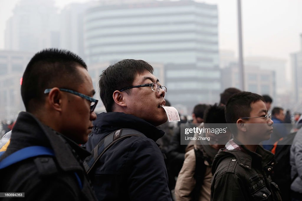 A man holding a ticket in his mouth arrives at the Beijing Railway Station on February 3, 2013 in Beijing, China. The Spring Festival travel season runs from January 26 to March 6 and according to reports road passenger transport in China is estimated at 3.1 billion people during this time of year.