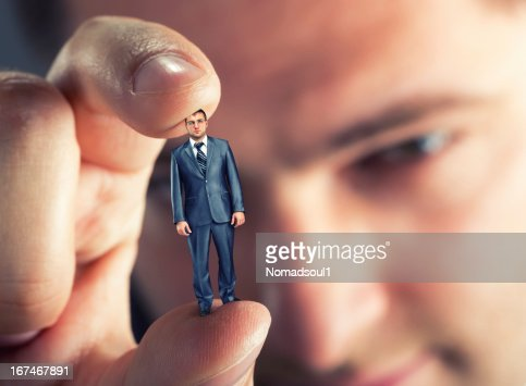 A man holding a tiny businessman between his fingers : Stock Photo