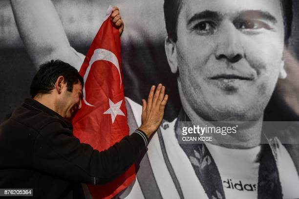 TOPSHOT A man holding a Turkish fag mourns on the portrait of Turkey's legendary triple Olympic goldmedal winning weightlifter Naim Suleymanoglu in...